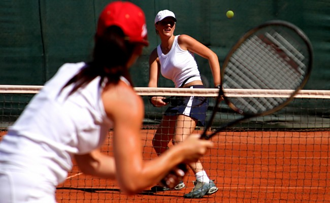 Two young sporty female tennis players having a game in the sun.